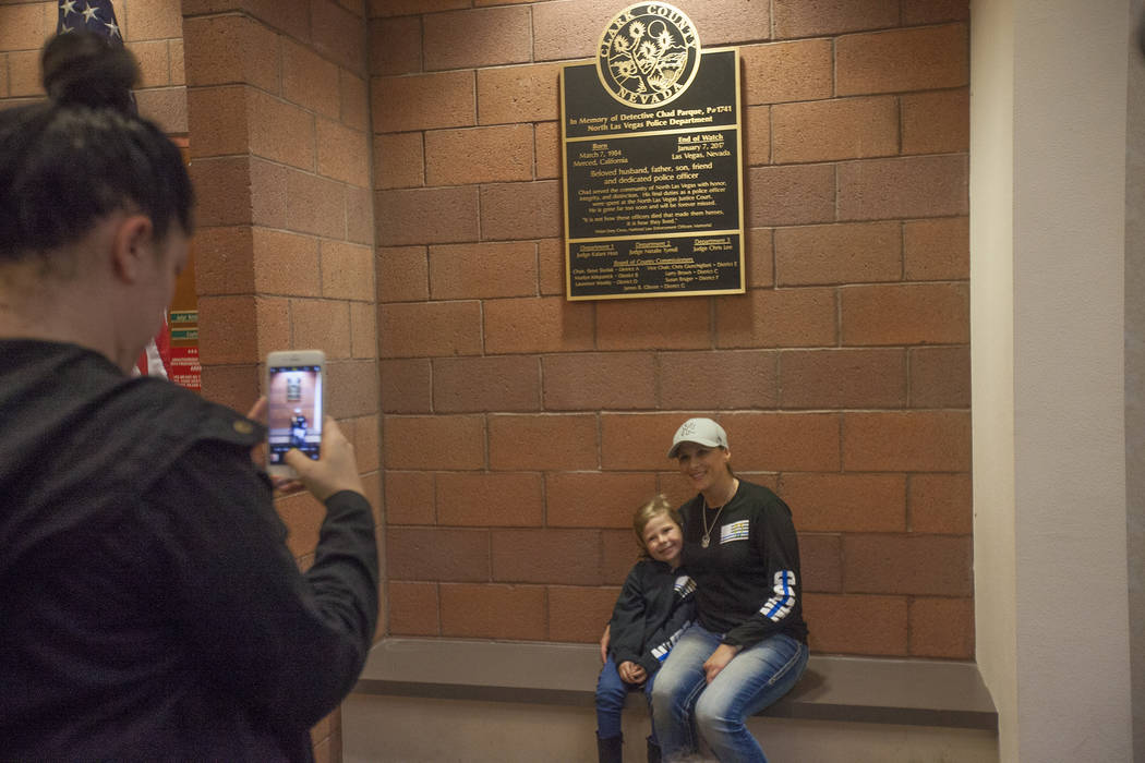 Rachel Lewis takes a photo of Jessica Parque, widow of Chad Parque, as she poses for a photo with her daughter Riley Parque in front of a plaque given in her late husband's honor at a memorial at  ...