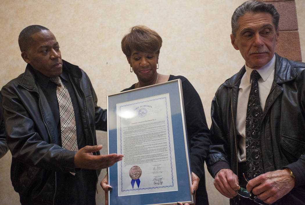 Clark County Commissioner Lawrence Weekly, from left, Councilwoman Pamela Goynes Brown, and Mayor pro-tem Richard Cherchio, hold a copy of a resolution that was given in honor of Chad Parque at a  ...