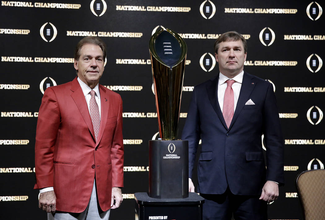 Alabama head coach Nick Saban, left, and Georgia head coach Kirby Smart pose with the NCAA college football championship trophy at a press conference in Atlanta, Sunday, Jan. 7, 2018. Georgia and  ...