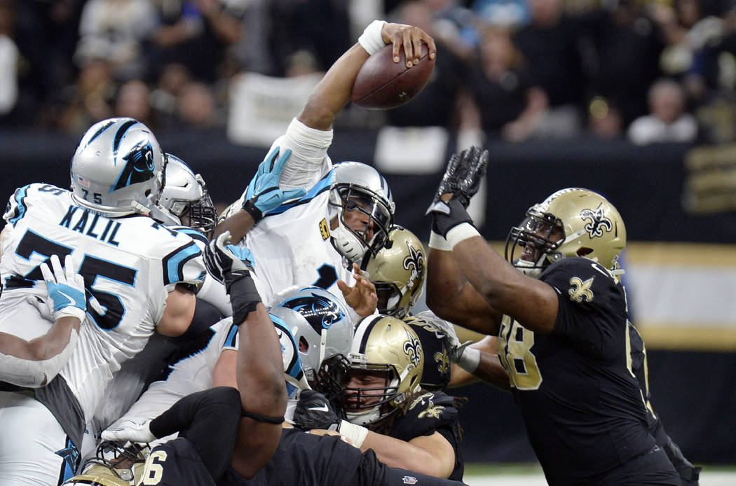 Carolina Panthers quarterback Cam Newton (1) reaches over the pile for a first down in the first half of an NFL football game against the New Orleans Saints in New Orleans, Sunday, Jan. 7, 2018. ( ...