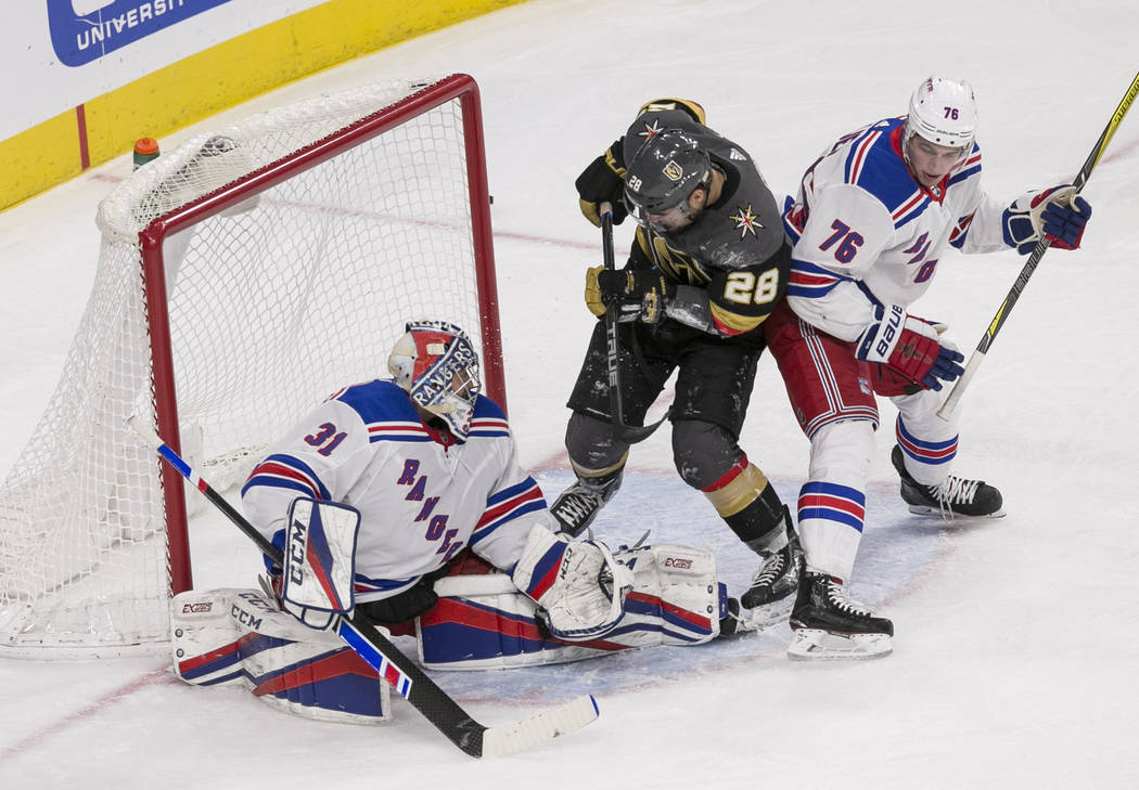 New York Rangers goaltender Ondrej Pavelec (31) blocks a shot by Vegas Golden Knights left wing William Carrier (28) as New York Rangers defenseman Brady Skjei (76) defends during the first period ...