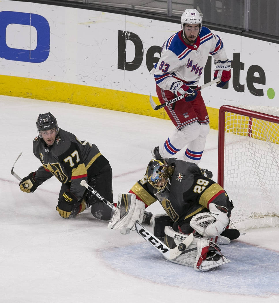 Vegas Golden Knights goaltender Marc-Andre Fleury (29) blocks a shot as Knights defenseman Brad Hunt (77) looks on during the first period of an NHL hockey game between the Vegas Golden Knights an ...