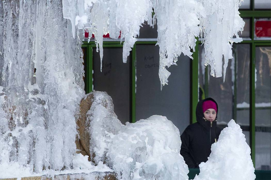 A woman passes an ice-covered fountain in New York's Bryant Park, Friday, Jan. 5, 2018. Frigid temperatures, some that could feel as cold as minus 30 degrees, moved across the East Coast on Friday ...