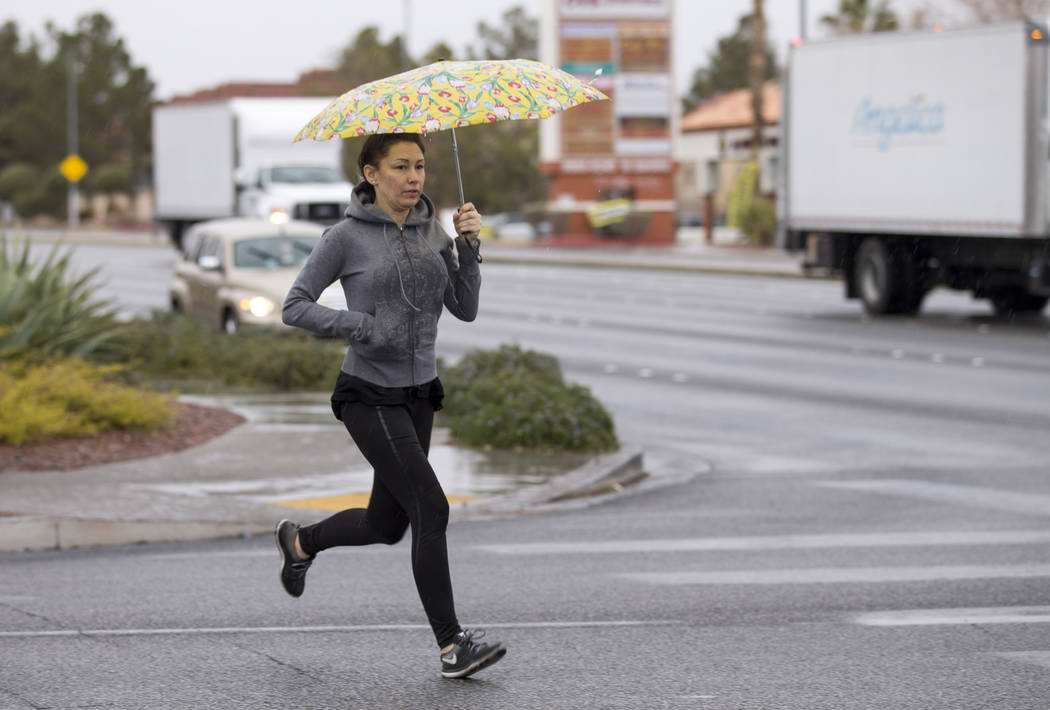 A woman runs as she shelters from the rain near S. Fort Apache Road and W. Sahara Avenue in Las Vegas on Monday, Jan. 8, 2018. Richard Brian Las Vegas Review-Journal @vegasphotograph