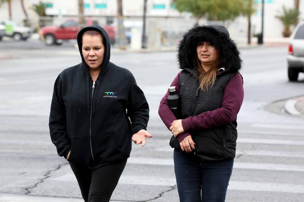 Jessica Fivas, left and Michelle Ovando, both of Las Vegas, walk across Las Vegas Boulevard at East Bridger Avenue in downtown Las Vegas during a light rain on Monday, Jan. 8, 2018. K.M. Cannon La ...