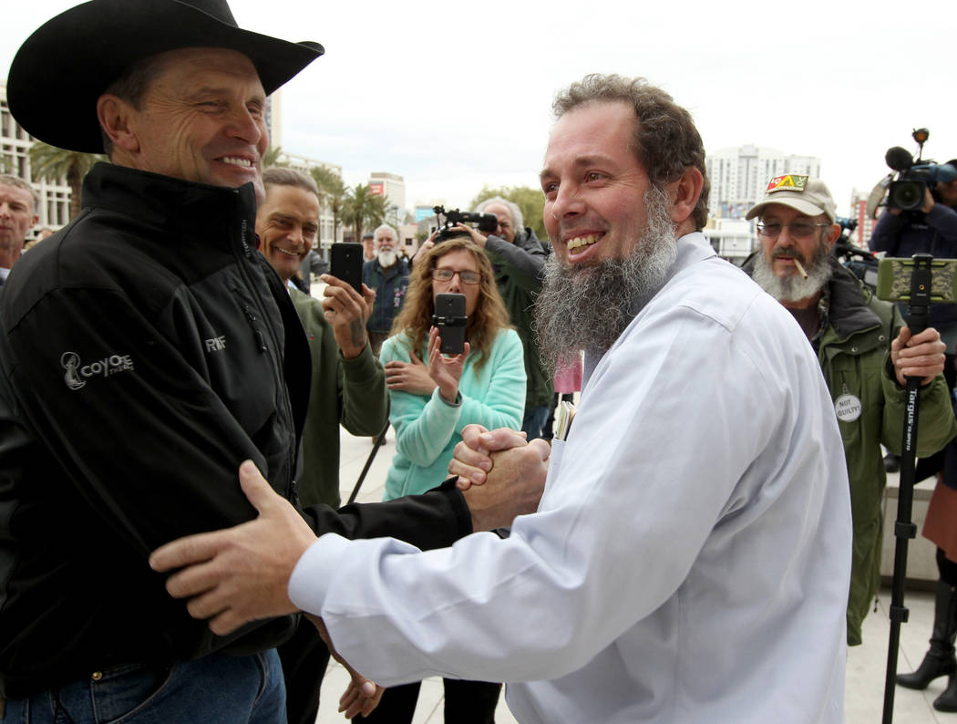 Cliven Bundy supporters Michael Bronson, left, and John Lamb hug outside Lloyd George U.S. Courthouse in Las Vegas Monday, Jan. 8, 2017, after a federal judge dismissed the case with prejudice aga ...