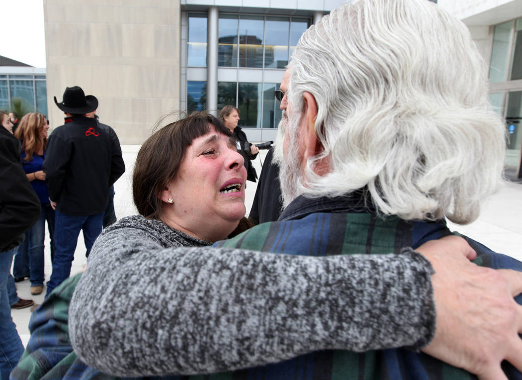 Cliven Bundy supporters Maggie Rose McGrath and Brand Thornton hug outside Lloyd George U.S. Courthouse in Las Vegas Monday, Jan. 8, 2017, after a federal judge dismissed the case with prejudice a ...