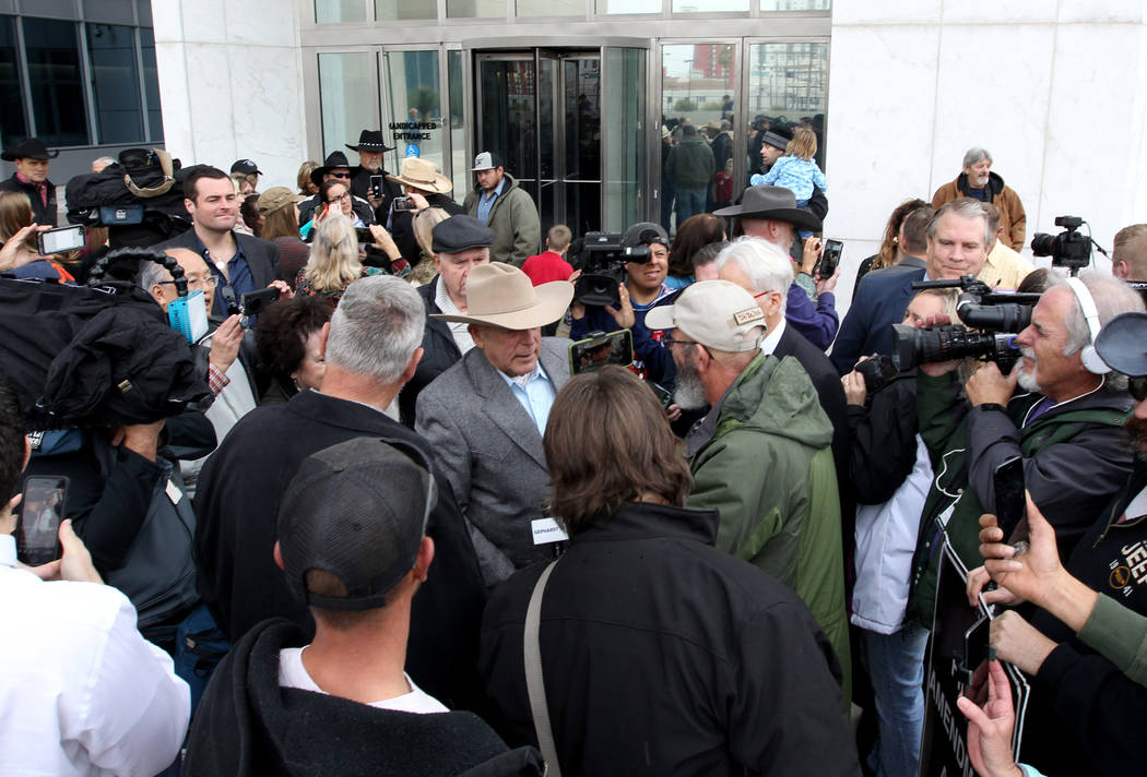 Cliven Bundy, center, talks to the news media after walking out of Lloyd George U.S. Courthouse in Las Vegas a free man Monday, Jan. 8, 2017, after a federal judge dismissed the case with prejudic ...