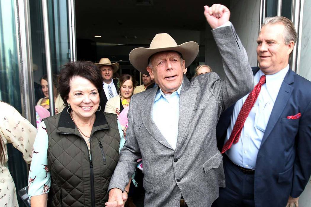 Cliven Bundy holds the hand of his wife, Carol, as he walks out of federal courthouse in Las Vegas for first time in nearly two years, Monday, Jan. 8, 2018. (Kevin Cannon/Las Vegas Review-Journal)