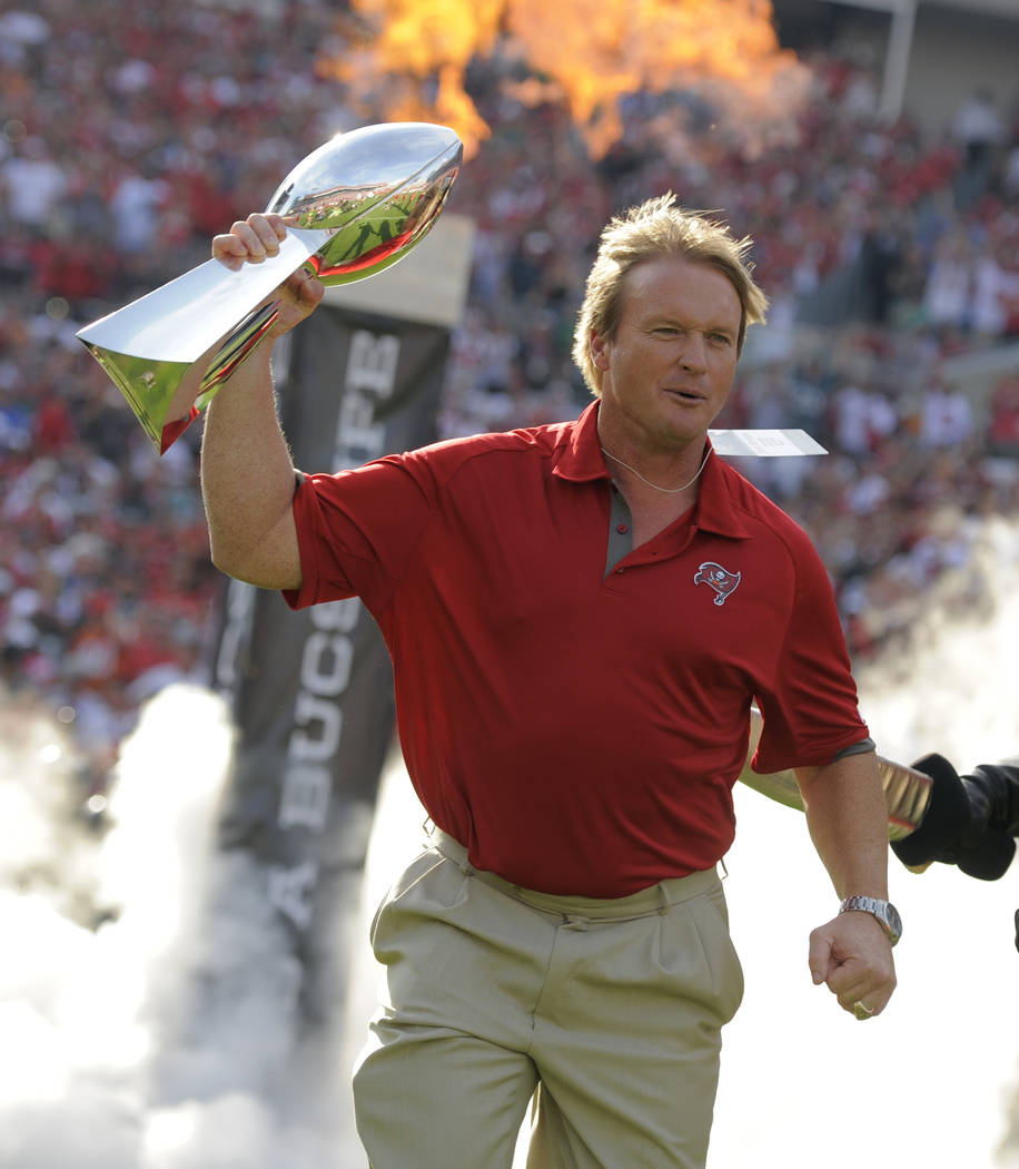 FILE - In this Dec. 9, 2012, file photo, former Tampa Bay Buccaneers and Oakland Raiders head coach Jon Gruden carries a Super Bowl trophy onto the field during halftime of an NFL football game as ...