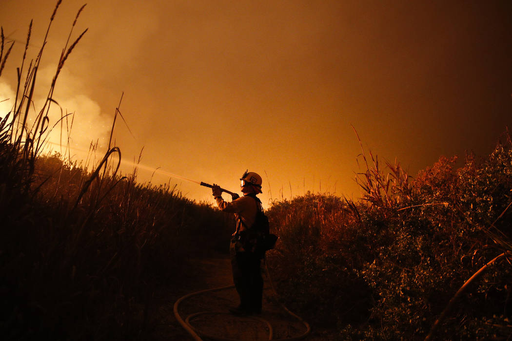 Firefighter Ryan Spencer battles a wildfire as it burns along a hillside toward homes in La Conchita, Calif., Dec. 7, 2017. (Jae C. Hong/AP Photo, File)