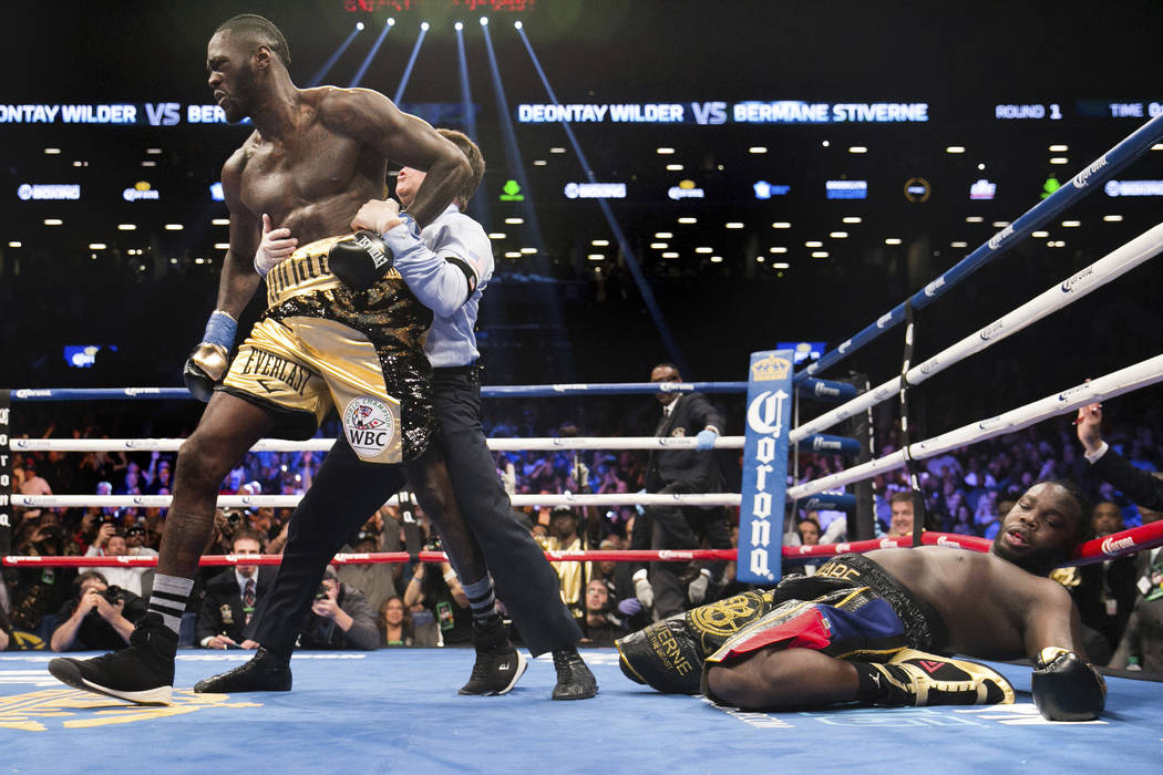 A referee pulls Deontay Wilder away from Bermane Stiverne after Wilder knocked out Stiverne during the WBC Heavyweight World Championship fight Saturday, Nov. 4, 2017, in New York. (AP Photo/Kevin ...