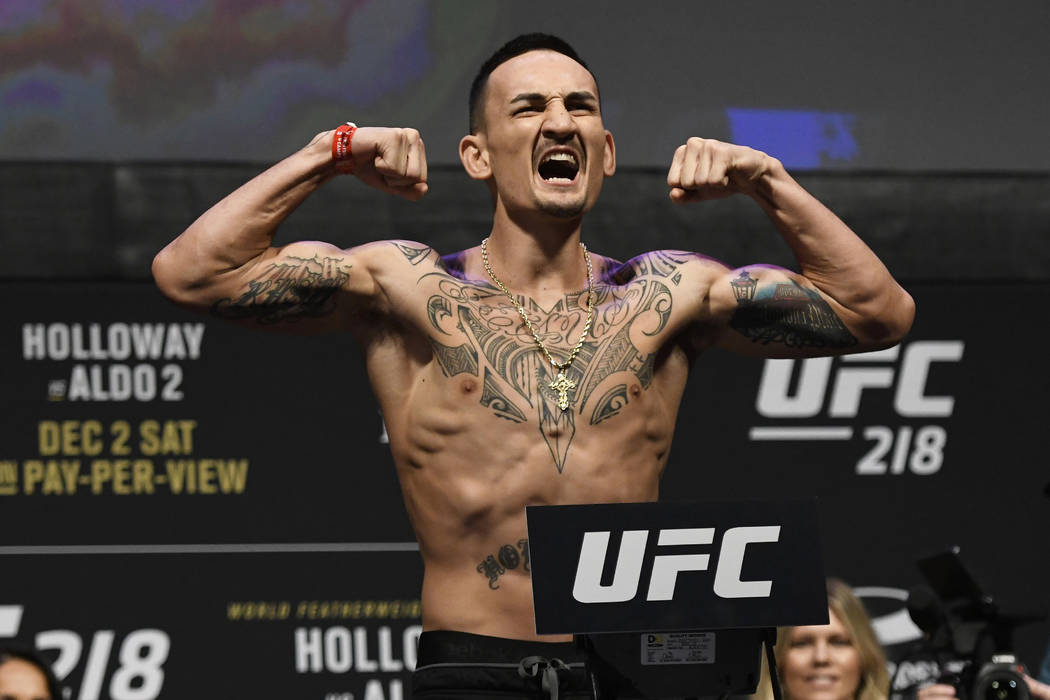 UFC featherweight champion Max Holloway reacts for the crowd during a weigh-in for a mixed martial arts match against Jose Aldo, Friday, Dec. 1, 2017, in Detroit. (Jose Juarez/AP Photo)