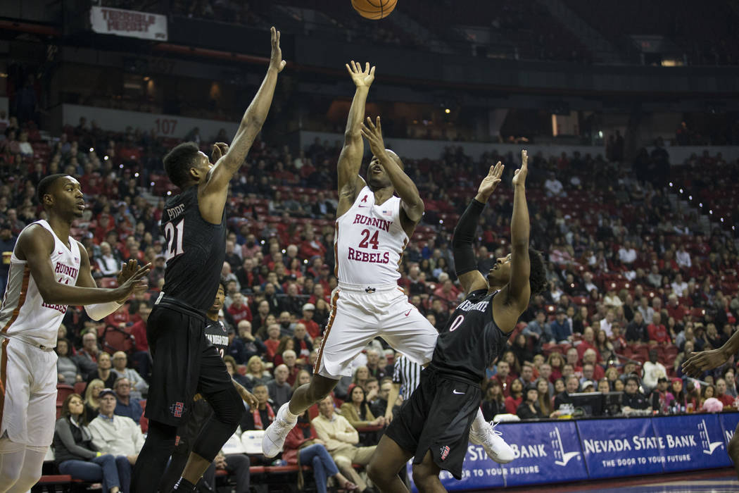 UNLV Rebels guard Jordan Johnson (24) takes a jump shot against San Diego State Aztecs forward Malik Pope (21) and guard Devin Watson (0) at the Thomas & Mack Center in Las Vegas, Saturday, Ja ...