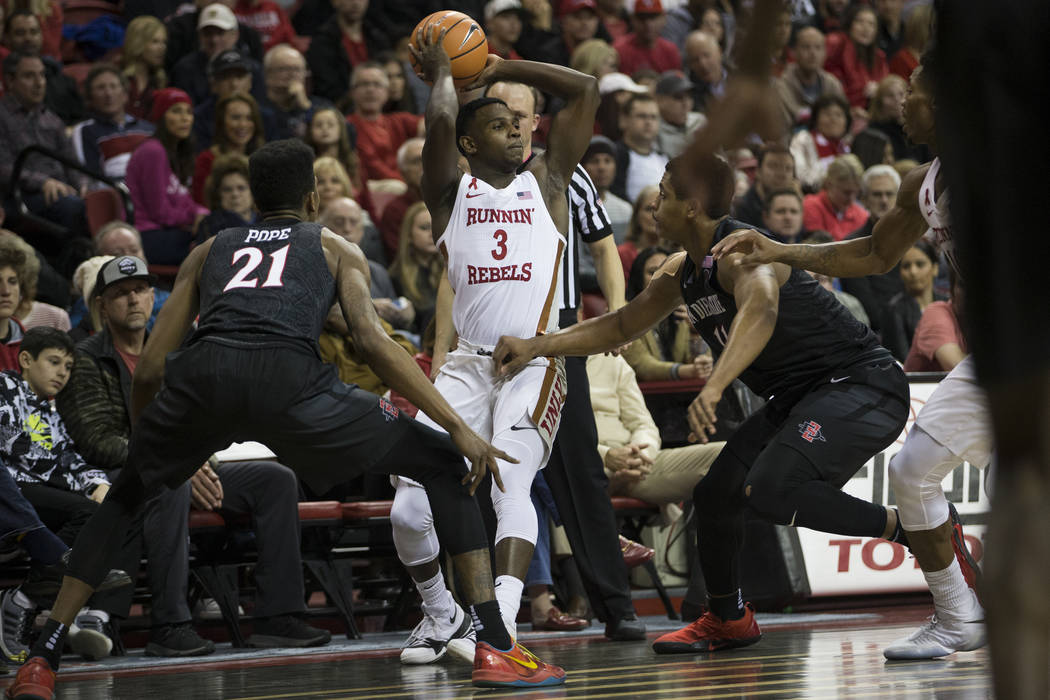 UNLV Rebels guard Amauri Hardy (3) looks for an open pass against pressure from San Diego State Aztecs forward Malik Pope (21) and forward Matt Mitchell (11) at the Thomas & Mack Center in Las ...