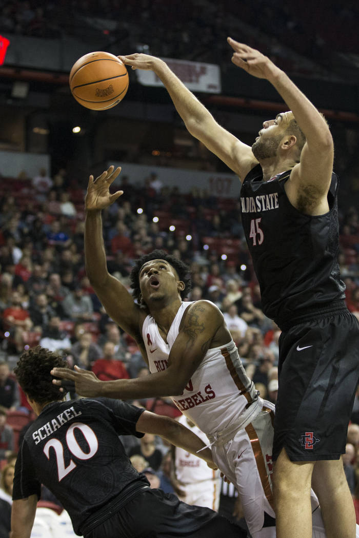 UNLV Rebels guard Jovan Mooring (30) shoots the ball against San Diego State Aztecs guard Jordan Schakel (20) and center Kameron Rooks (45) at the Thomas & Mack Center in Las Vegas, Saturday,  ...
