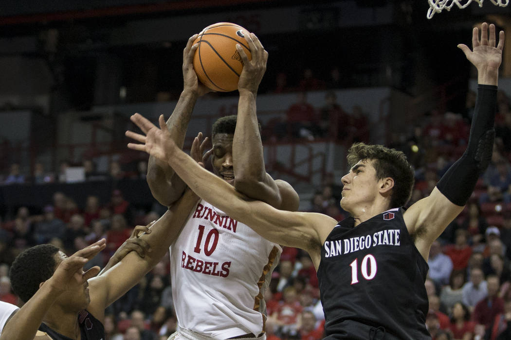 UNLV Rebels forward Shakur Juiston (10) is fouled as he goes up for a shot against San Diego State Aztecs forward Matt Mitchell (11) and forward Max Montana (10) at the Thomas & Mack Center in ...