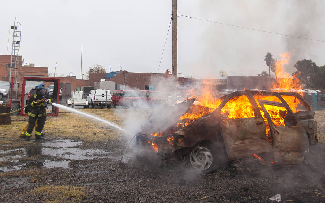 New recruits put out a car fire at the Las Vegas Fire Department Training facilities in Las Vegas, Tuesday, Jan. 9, 2018. The new recruits, in their 13th week of the Fire Academy, were given a rea ...