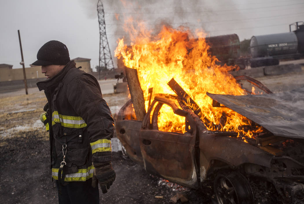 Firefighter Micah Reyes walks away from a car after unloading wood in it to allow it to burn at the Las Vegas Fire Department Training facilities in Las Vegas, Tuesday, Jan. 9, 2018. He helped tea ...