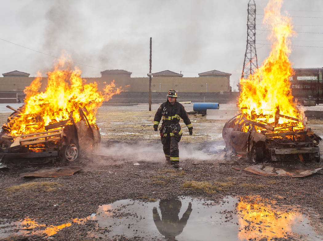 Firefighter Jeff Simone walks between two cars on fire at the Las Vegas Fire Department Training facilities in Las Vegas, Tuesday, Jan. 9, 2018. He was helping train new recruits, in their 13th we ...