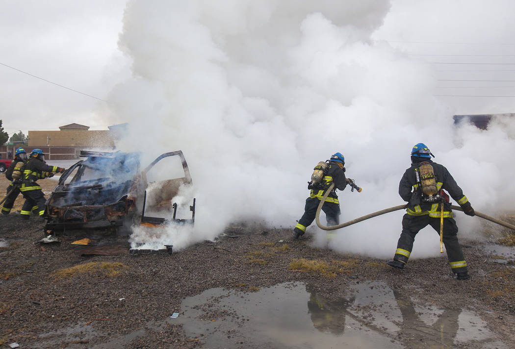 Firefighter recruit Andrew Stalker is backing up fellow recruit Jason Coats as fellow recruits Devon Turner and Andrew Christie work on another car fire at the Las Vegas Fire Department Training f ...