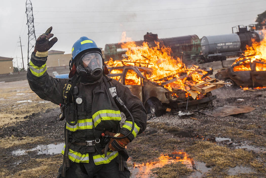 Firefighter recruit Devon Turner signals to other recruits before they wash out a car fire at the Las Vegas Fire Department Training facilities in Las Vegas, Tuesday, Jan. 9, 2018. New recruits, i ...