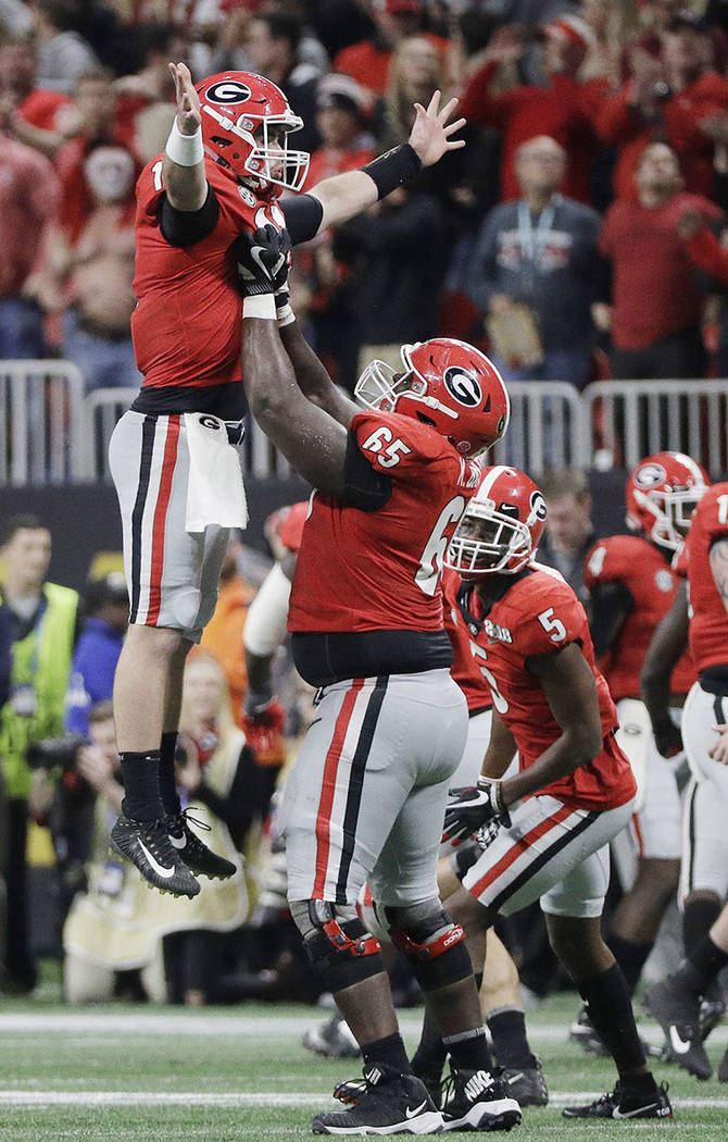 Georgia's Kendall Baker lifts quarterback Jake Fromm (11) after a long touchdown pass during the second half of the NCAA college football playoff championship game against Alabama Monday, Jan. 8,  ...