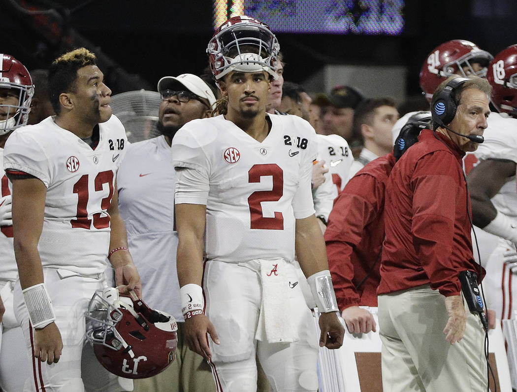 Alabama's Jalen Hurts (2) is seen on the bench with Tua Tagovailoa (13) head coach Nick Saban during the second half of the NCAA college football playoff championship game against Georgia Monday,  ...