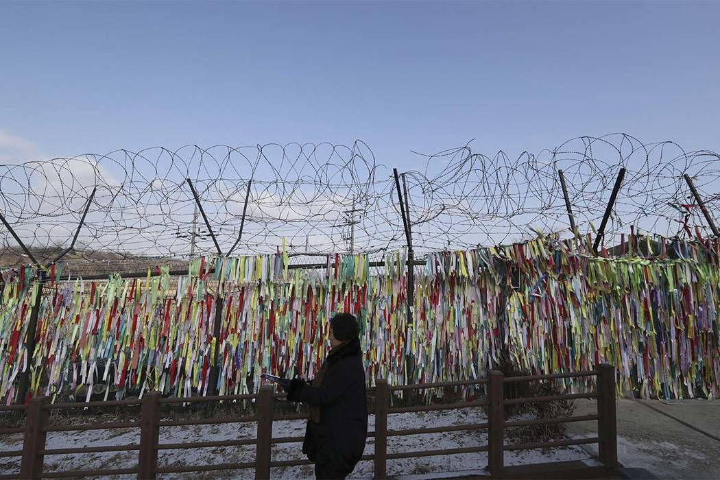 A visitor walks by the wire fence decorated with ribbons carrying messages to wish for the reunification of the two Koreas at the Imjingak Pavilion in Paju, South Korea, Tuesday, Jan. 9, 2018. (Le ...