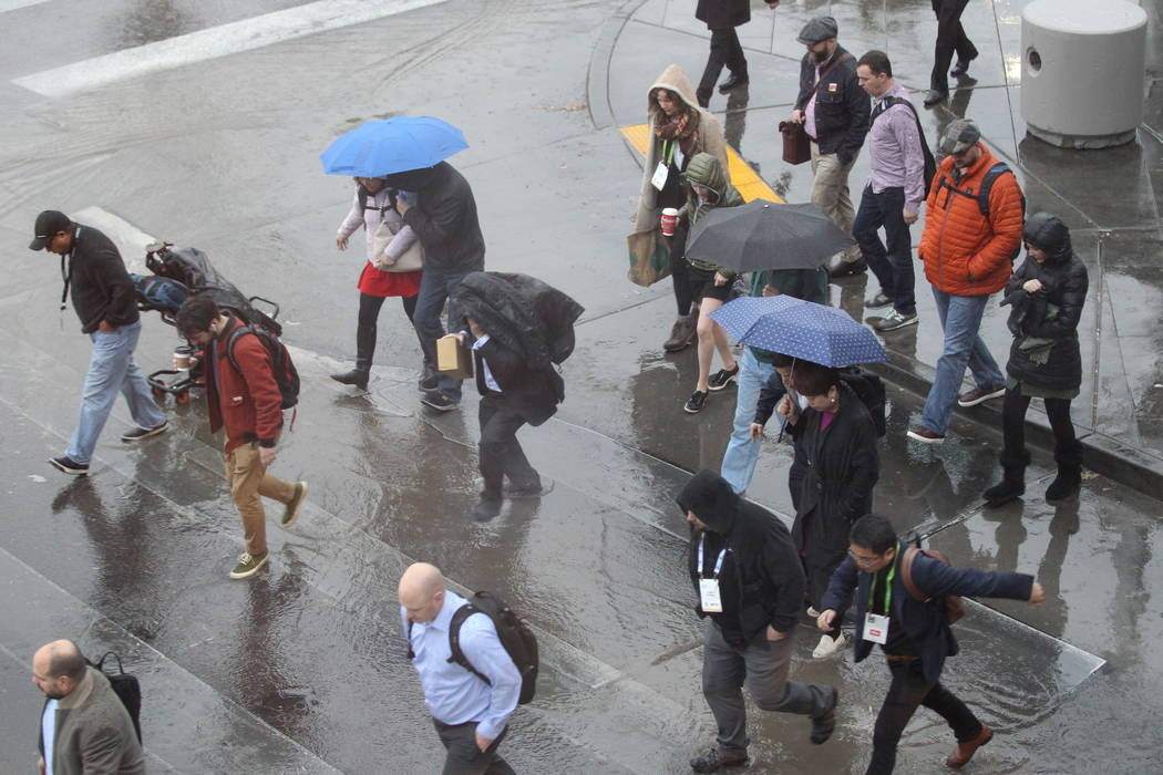 Attendees cross Paradise Road to the Consumer Electronics Show at the Las Vegas Convention Center during a rain storm on Tuesday, Jan. 10, 2018. K.M. Cannon Las Vegas Review-Journal @KMCannonPhoto