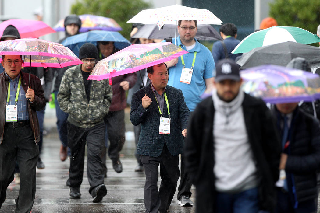Attendees cross Paradise Road to CES at the Las Vegas Convention Center during a rain storm on Tuesday, Jan. 10, 2018. (K.M. Cannon/Las Vegas Review-Journal) @KMCannonPhoto