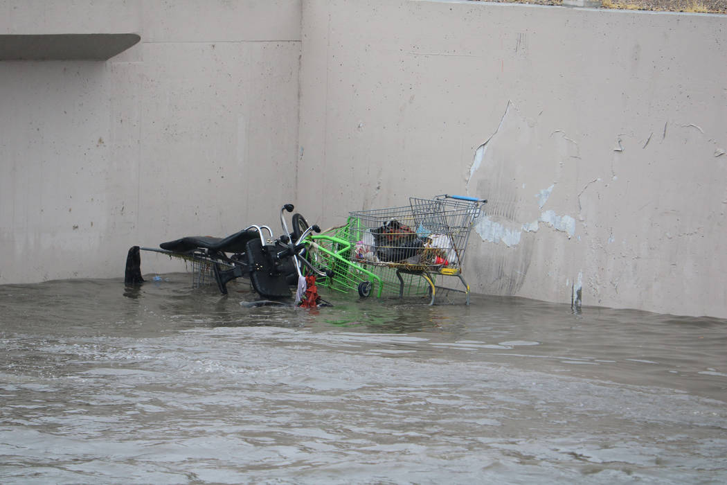 Shopping carts are half-submerged in floodwaters about 100 yards below the site where crews rescued a man and a woman under a bridge on east Carey Avenue along the Las Vegas Wash on Tuesday, Jan.  ...