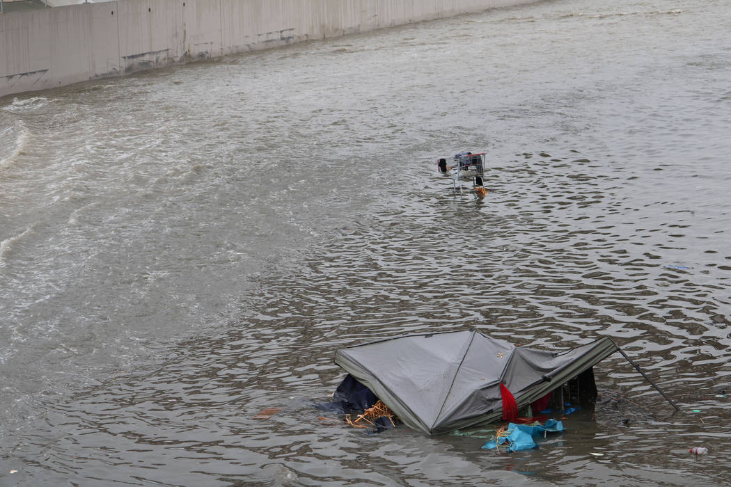 A tent and a shopping cart are caught in floodwaters above a detention basin near east Cheyenne Avenue along the Las Vegas Wash on Tuesday, Jan. 9, 2018. About a mile downstream, rescue crews came ...