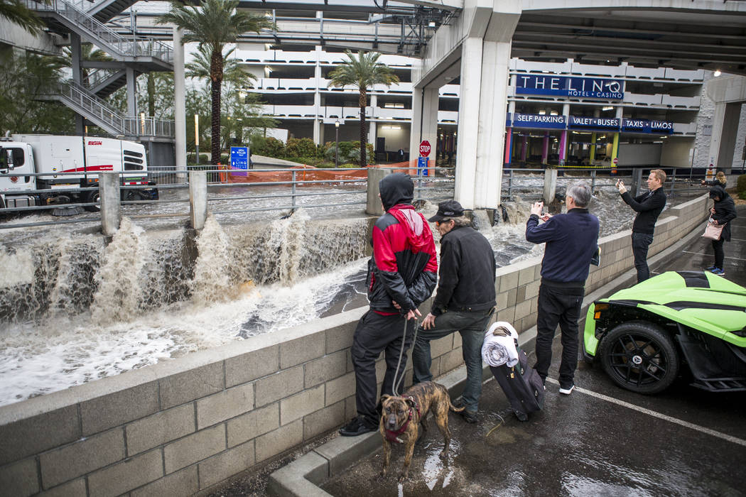 People watch floodwaters rush by in a flood channel near The Linq Hotel in Las Vegas on Tuesday, Jan. 9, 2018. (Patrick Connolly/Las Vegas Review-Journal) @PConnPie