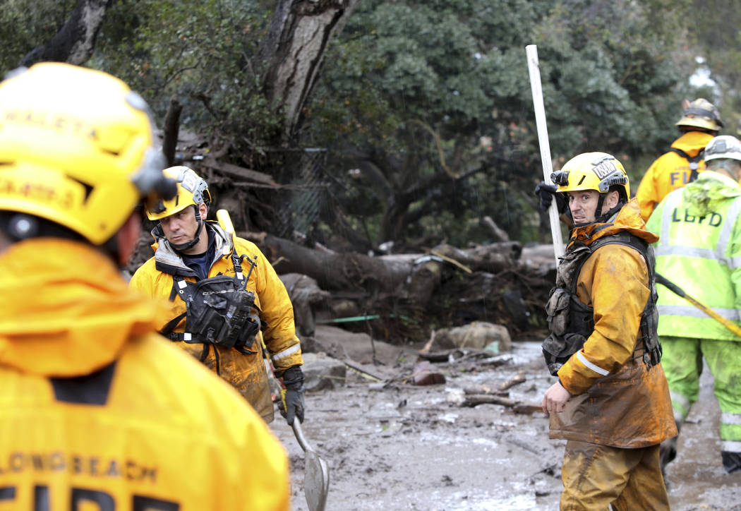 Members of the Long Beach Search and Rescue team head into a debris-soaked area of Montecito, Calif. to look for survivors on Tuesday, Jan. 9, 2018. Several homes were swept away before dawn Tuesd ...