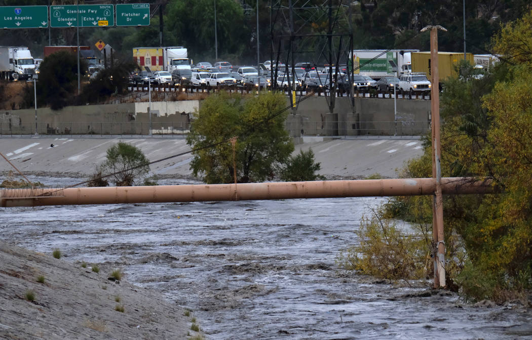 Northbound traffic comes to a standstill on Interstate 5 freeway near the rushing water filled Los Angeles river near downtown Los Angeles on Tuesday, Dec. 9, 2018. The first significant storm of  ...