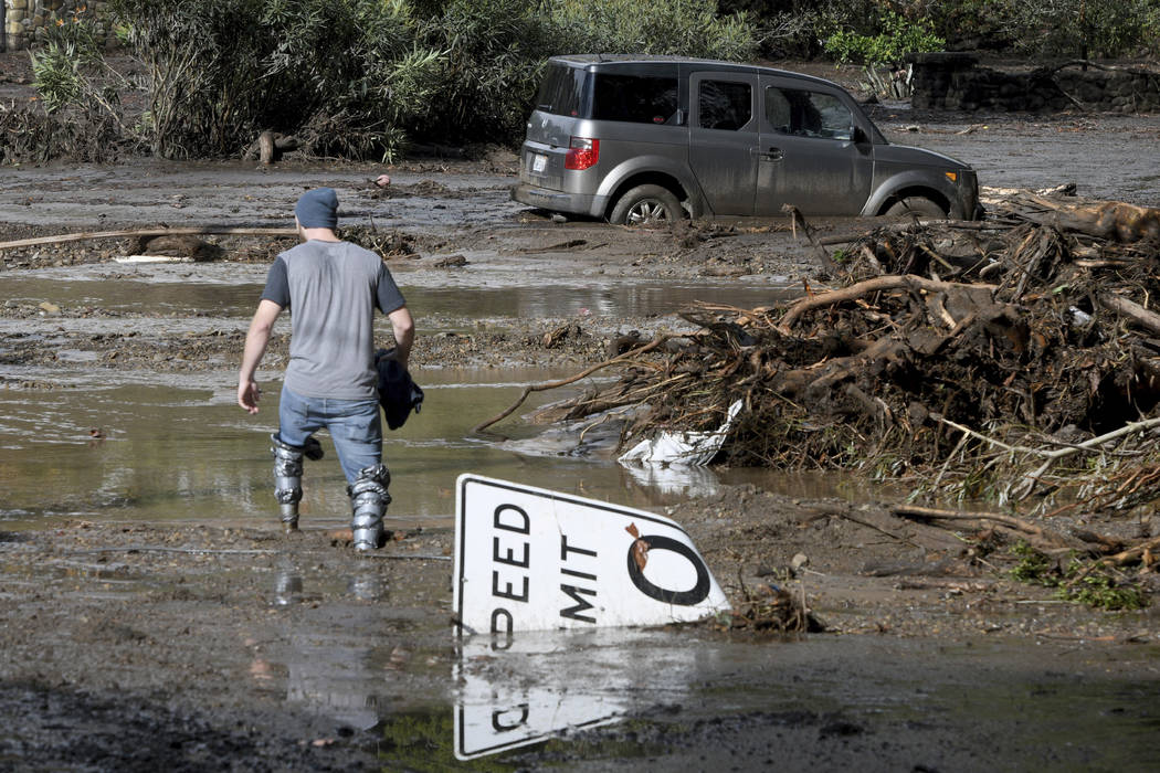 Mitchell Barrett crosses mud from an overflown creek on Sheffield Drive in Montecito, Calif., following the heavy rain, Tuesday, Jan. 9, 2018. Barrett was going to check on his parents' house in M ...
