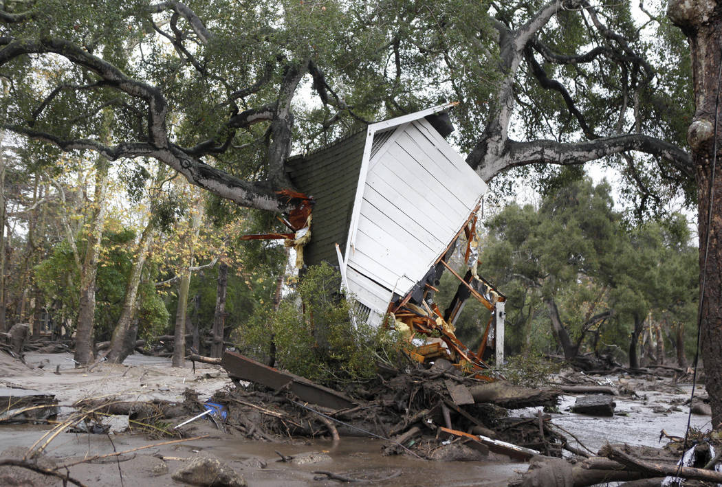 A structure is smashed against a tree along Hot Springs Road in Montecito, Calif. after getting hit by a flash flood and debris flow on Tuesday, Jan. 9, 2018. Several homes were swept away before  ...