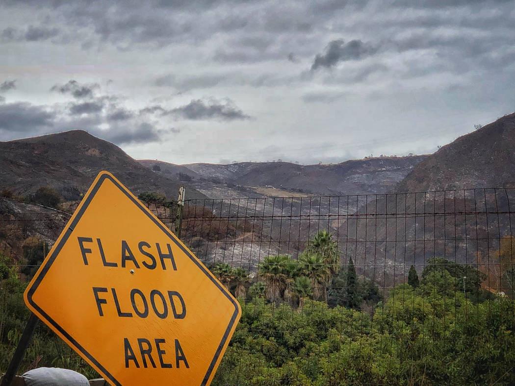 In this photo provided by Santa Barbara County Fire Department, a flash flood area sign is posted, as evacuations have been issued for several fire-ravaged communities in Santa Barbara, Calif., Mo ...