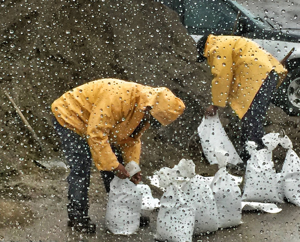 In this photo taken through a glass window, released by Santa Barbara County Fire Department, people fill up sandbags under the rain in Santa Barbara, Calif., Monday, Jan. 8, 2018. Storms brought  ...