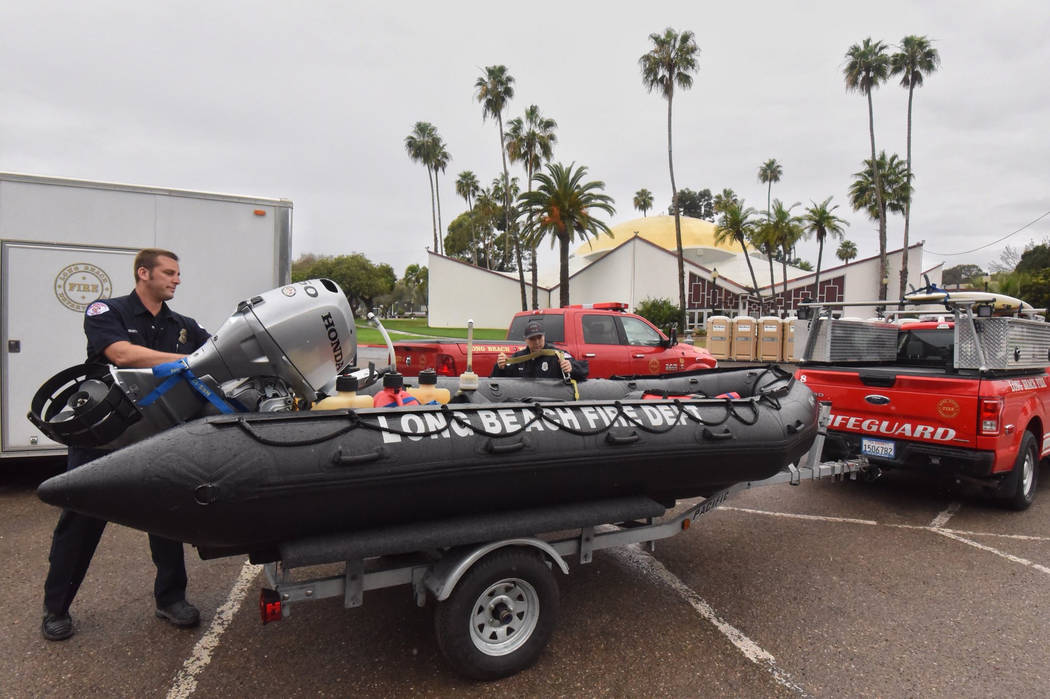 In this photo released by Santa Barbara County Fire Department, members of the Long Beach Fire Department Swift Water Rescue Team check equipment while staged at Earl Warren Showgrounds in Santa B ...