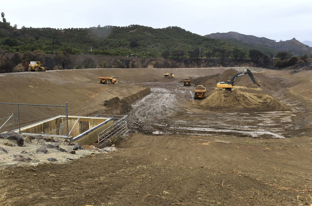 County workers remove dirt from the Adams Canyon debris basin as rain began to fall in Ventura County in Ventura, Calif., Monday, Jan. 8, 2018. To reduce the risk of damage from possible debris fl ...