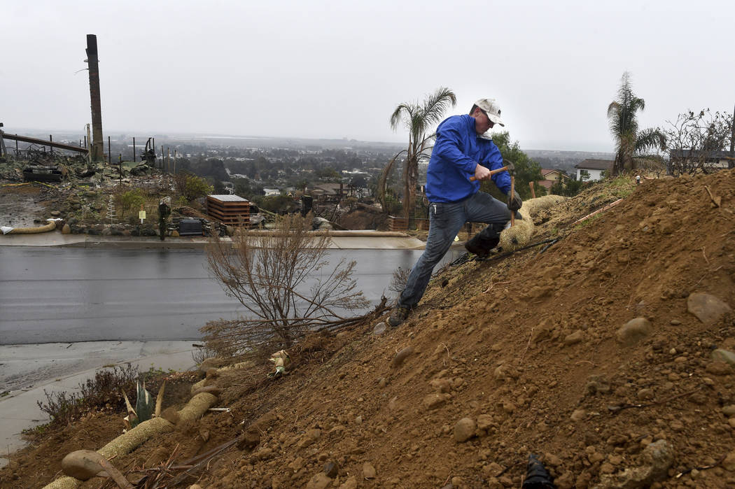 Kyle Field installs rain wattles around his property as rain started falling in the area in Ventura, Calif., on Monday, Jan. 8, 2018. Though Field's home was destroyed in the Thomas Fire, he plans ...
