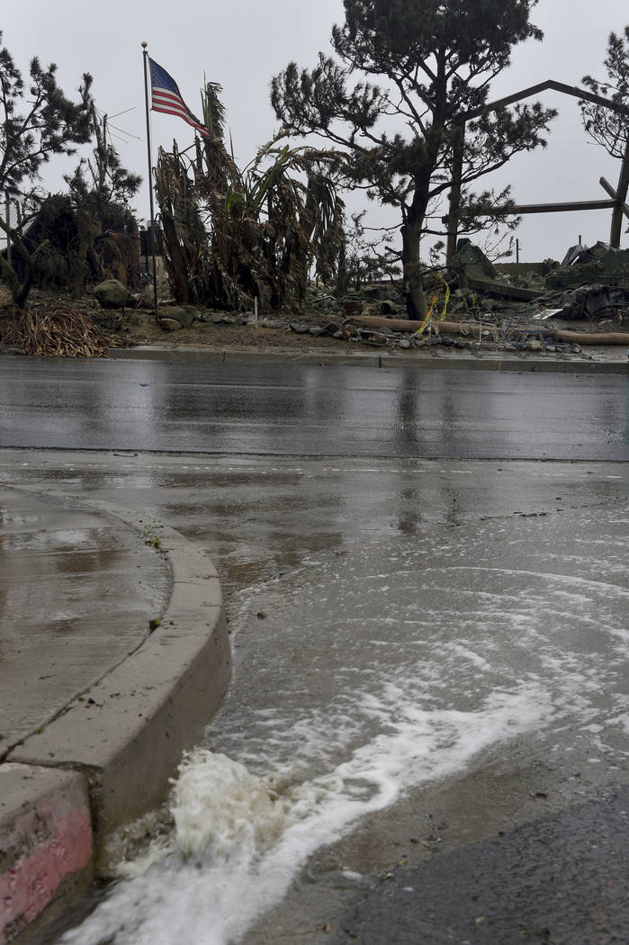 Rainwater flows down Alverstone Avenue in Ventura, Calif., Monday, Jan. 8, 2018. The wet and windy system moving ashore could soak much of the state and drop several inches in parts of Santa Barba ...