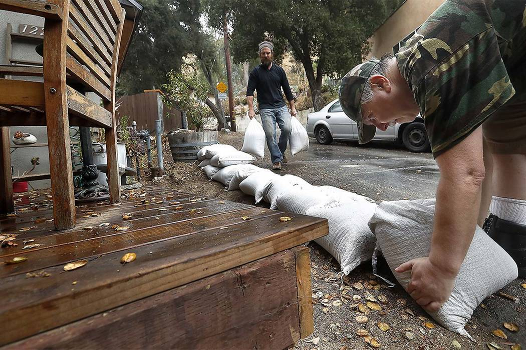 Jeremy Felch, left, gets help from his neighbor Ralf Quint, in placing sandbags in front of his home on Spring Trail in Kagel Canyon, in preparation for expected heavy rain. (Mel Melcon/Los Angele ...