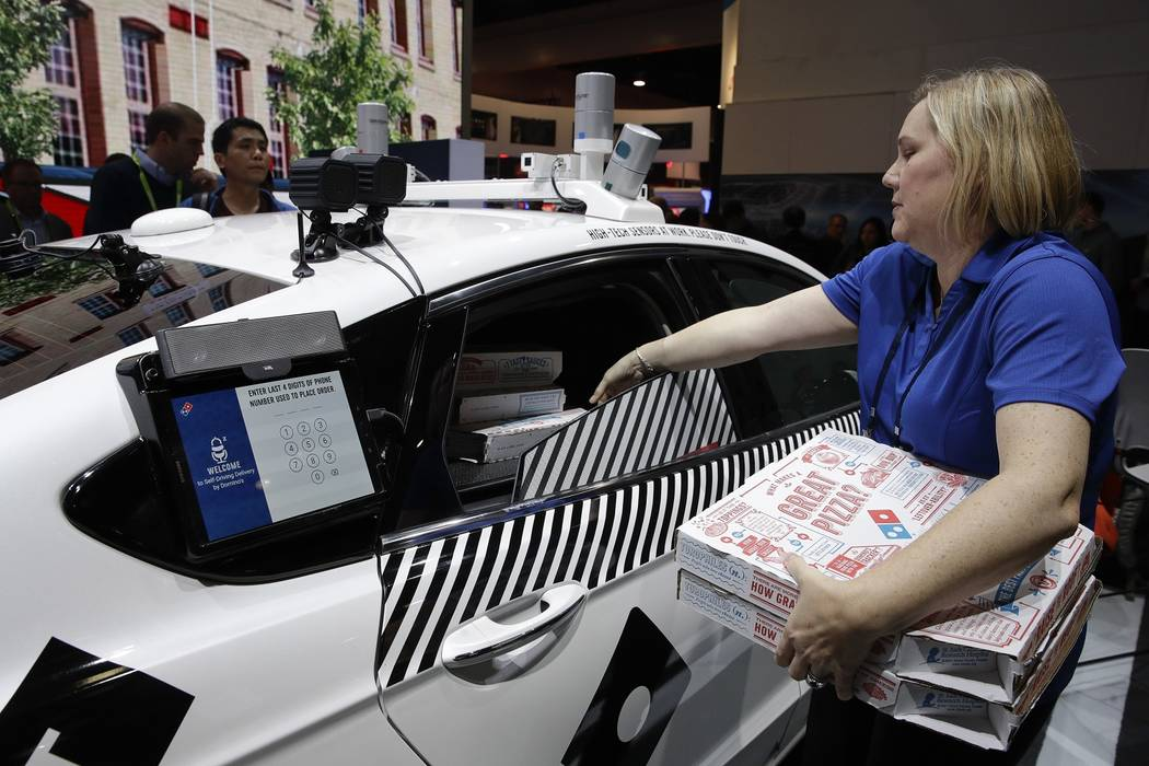 Jenny Fouracre puts pizza boxes into Ford's self-driving delivery vehicle at CES, Tuesday, Jan. 9, 2018, in Las Vegas. (Jae C. Hong/AP)