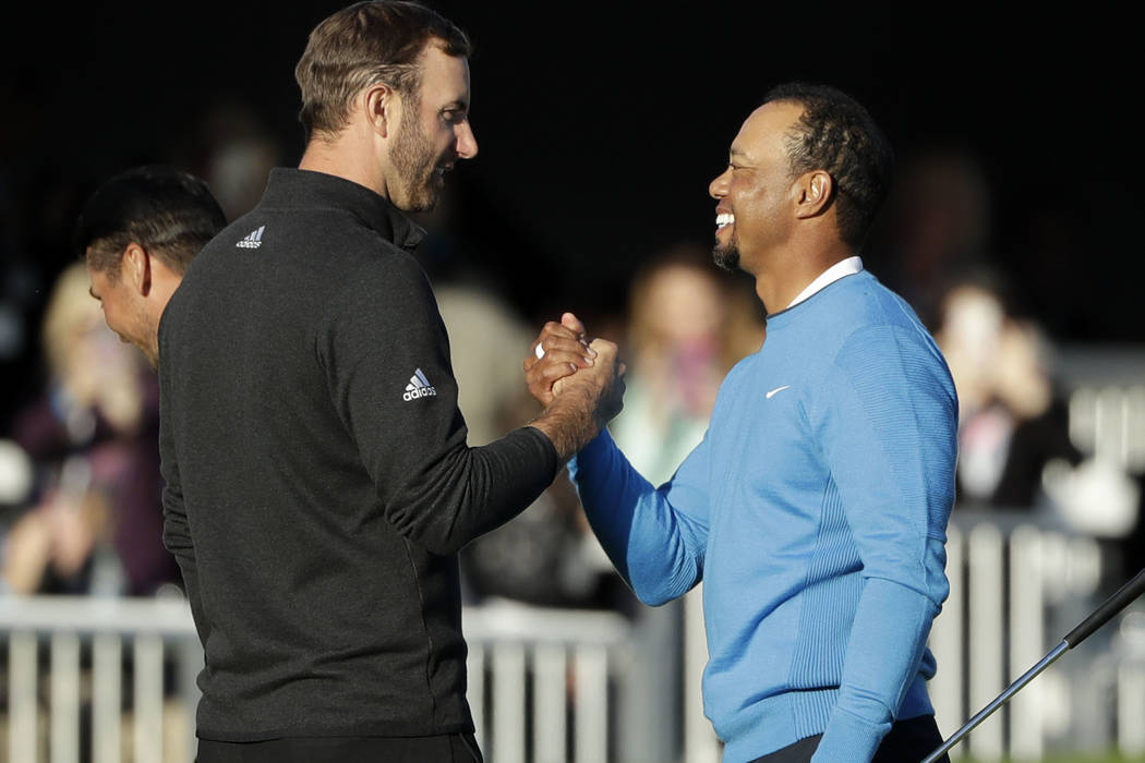 Tiger Woods, right, reacts with Dustin Johnson, left, after finishing on the 18th hole of the south course during the first round of the Farmers Insurance Open golf tournament Thursday, Jan. 26, 2 ...