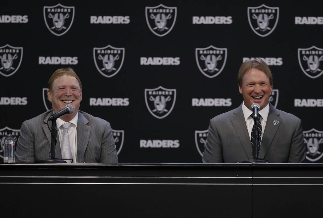 Oakland Raiders new head coach Jon Gruden, right, smiles as he listens to a question from former Raiders player Charles Woodson, as he sits next to owner Mark Davis during an NFL football press co ...