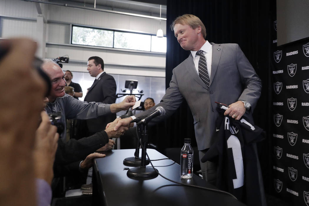 Oakland Raiders head coach Jon Gruden shakes hands with reporters after an NFL football press conference Tuesday, Jan. 9, 2018, in Alameda, Calif. (AP Photo/Marcio Jose Sanchez)