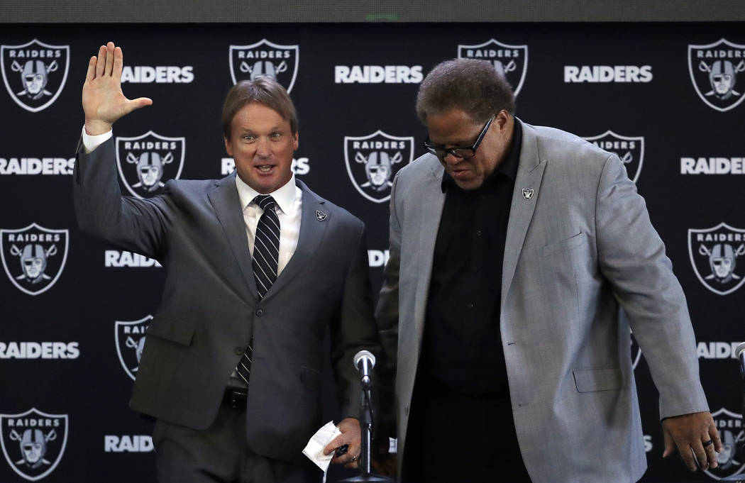 Oakland Raiders head coach Jon Gruden, left, waves next to general manager Reggie McKenzie during an NFL football press conference Tuesday, Jan. 9, 2018, in Alameda, Calif. (AP Photo/Marcio Jose S ...